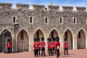 Windsor, United Kingdom - June 29, 2015: Changing the Guard at Windsor Castle, Berkshire England. Windsor castle was built in the 11th century and is the longest-occupied palace in Europe. Guards wearing vivid red uniform and carrying rifles are in the image.
