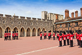 Windsor, United Kingdom - June 29, 2015: Queen's Guard (Royal Guard) at Windsor Castle, Berkshire England, United Kingdom. Windsor castle was built in the 11th century and is the longest-occupied palace in Europe. Guard wearing vivid red uniform, rifle and street lamp are in the image.