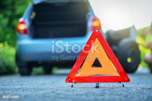 istock Changing the tire on broken car with red warning triangle 503714942