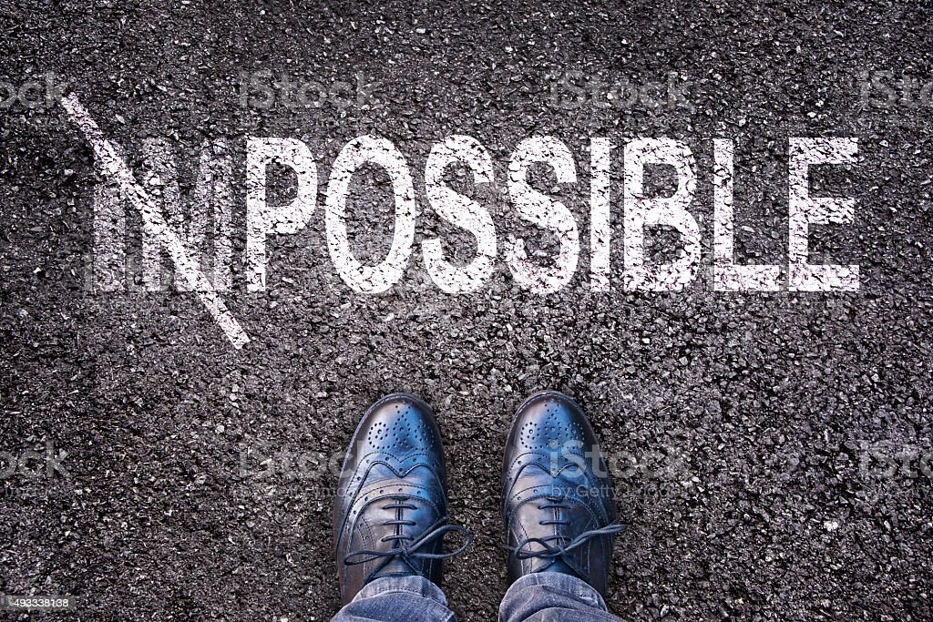 Changing the word impossible on possible on an aspahlt road stock photo