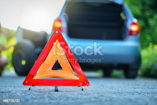104275470istockphoto Changing tire on broken car on road with warning triangle 468725732