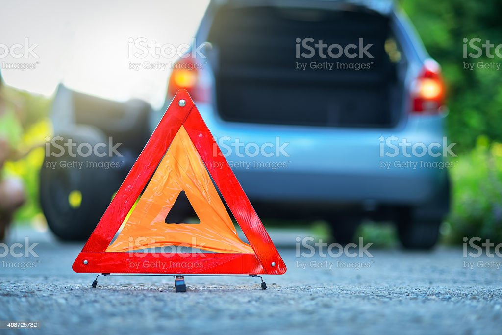 Changing tire on broken car on road with warning triangle stock photo