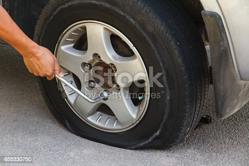 istock Changing tire with wheel wrench. 655330750