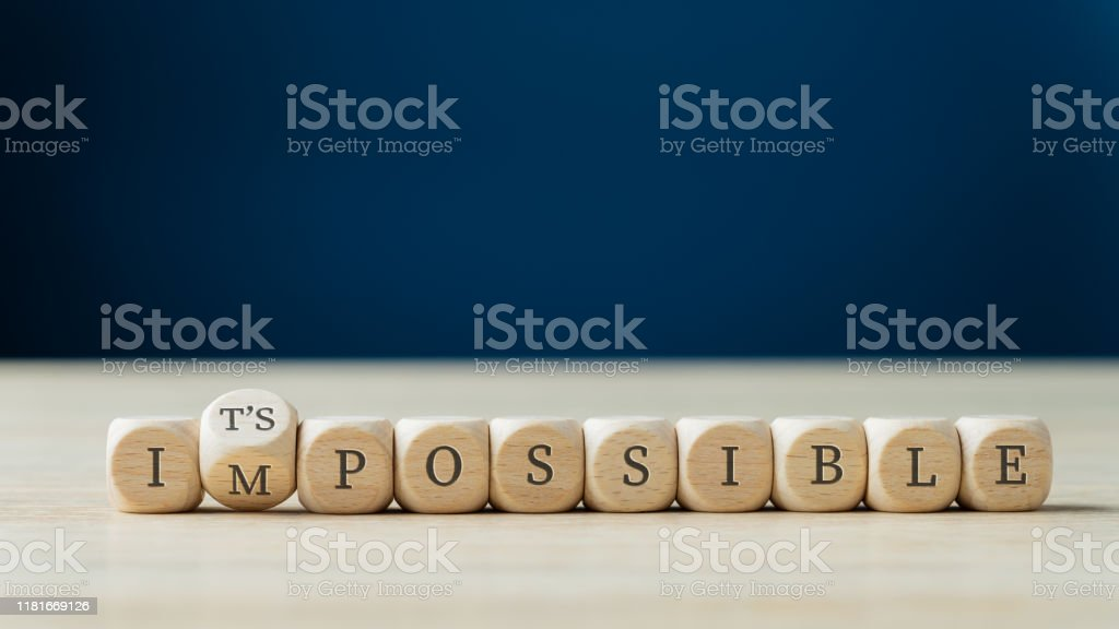 Changing word impossible into its possible Word impossible spelled on wooden dices with the second one turning to spell the Its possible sign. Achievement Stock Photo