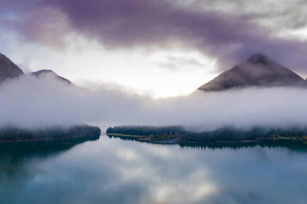 Kanal mit Brücke bei Dämmerung stagniert mit nebligen Wolken bei heiterwang austria – Foto