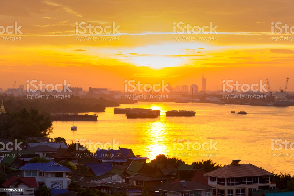 Chao Phraya river and Morning light reflections in the river in Bangkok landscape, with panorama cityscale with sunrise / sunset, light yellow and orange sky stock photo