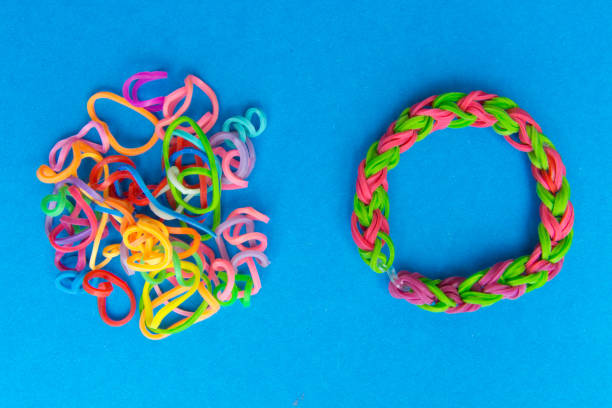 Chaos and order. Rubber bands for weaving loose and bracelet of rubber bands stock photo