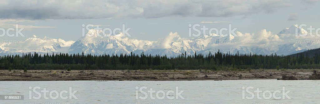 Chaos on riverbank with mountains in background royalty-free stock photo