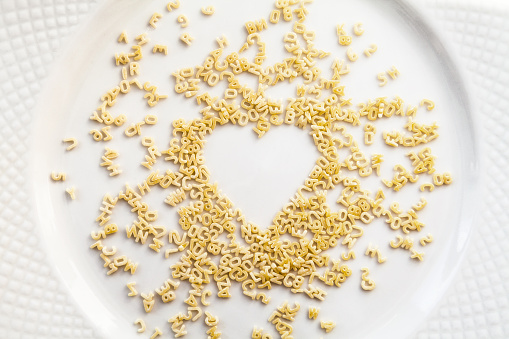 Chaotic alphabet pasta letters and numerals in a heart shape
