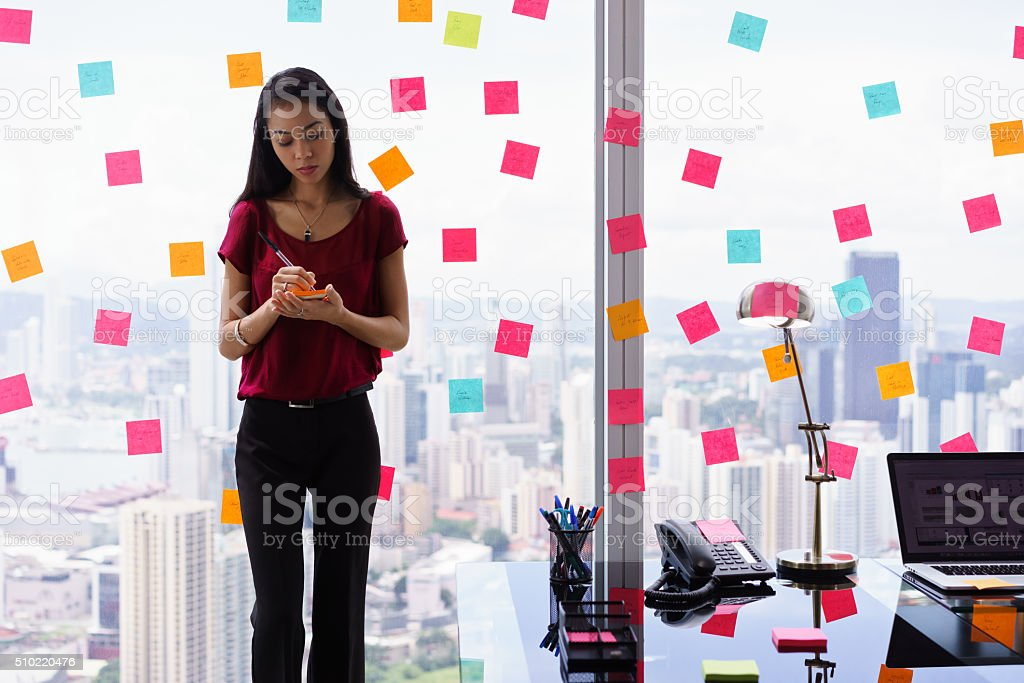 Chaotic Office With Secretary Writing Sticky Notes On Window stock photo