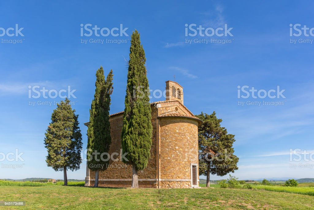 Chapel on a hill with cypress trees stock photo