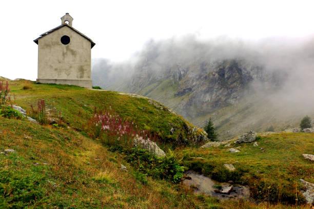 Kapelle auf dem Gipfel, kurzen Rasen, rosa Blüten, Bergbach bei Nebel und hohen Bergen in den Rücken – Foto
