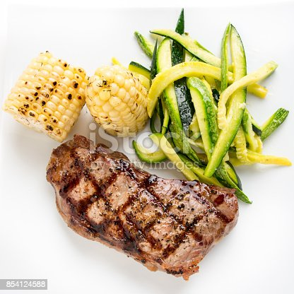 Char Grilled York Steak with sliced steamed zucchini and grilled corn on eje cob from above on white background
