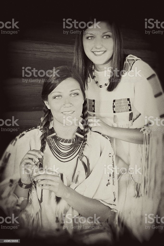 Character:  Young females portray Native American Indian culture. Sepia tone. royalty-free stock photo