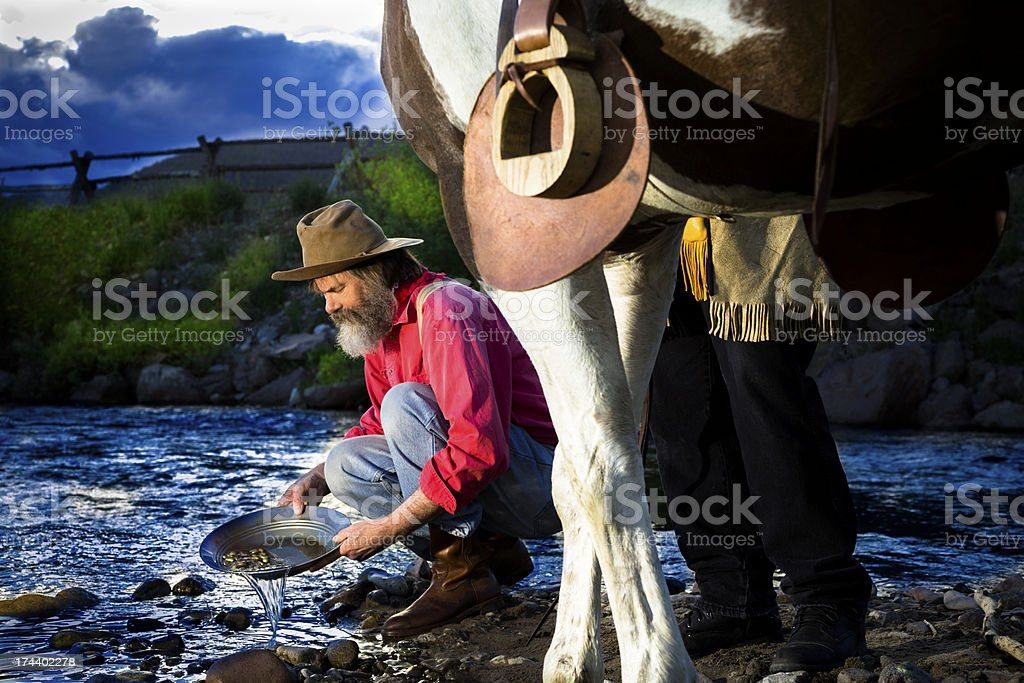 Characters: Gold Prospector pans in stream near mountain. stock photo