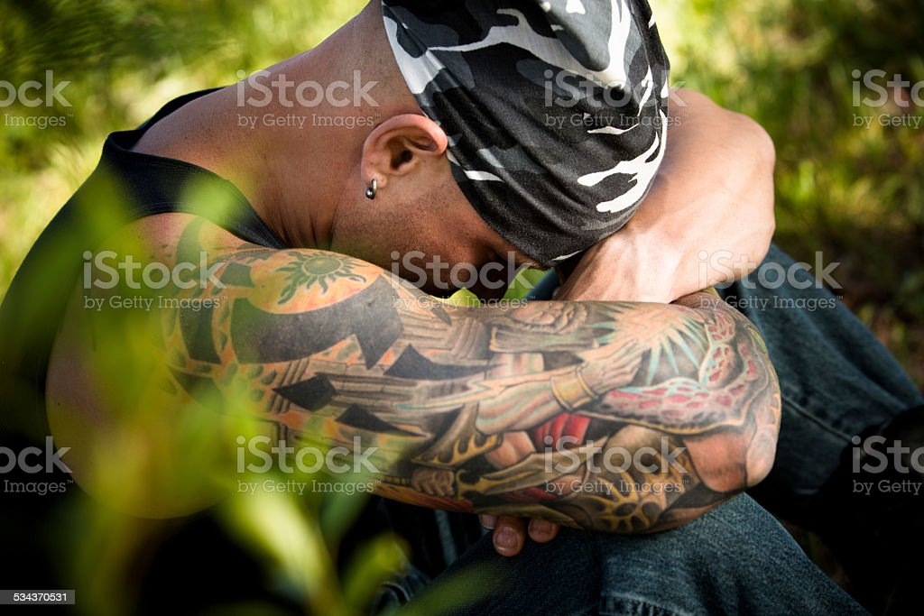 Characters: Sad man with tattoos and piercings contemplates. Nature. stock photo