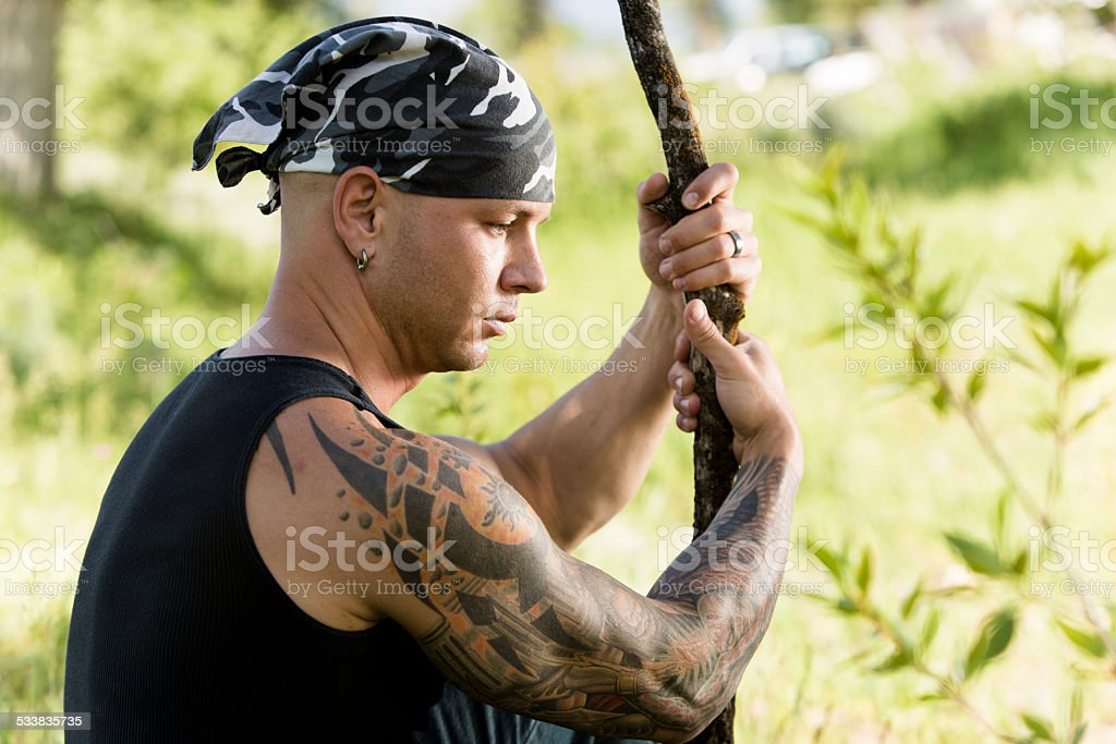 Characters: Tribal man with tattoos and piercings contemplates. Nature. stock photo