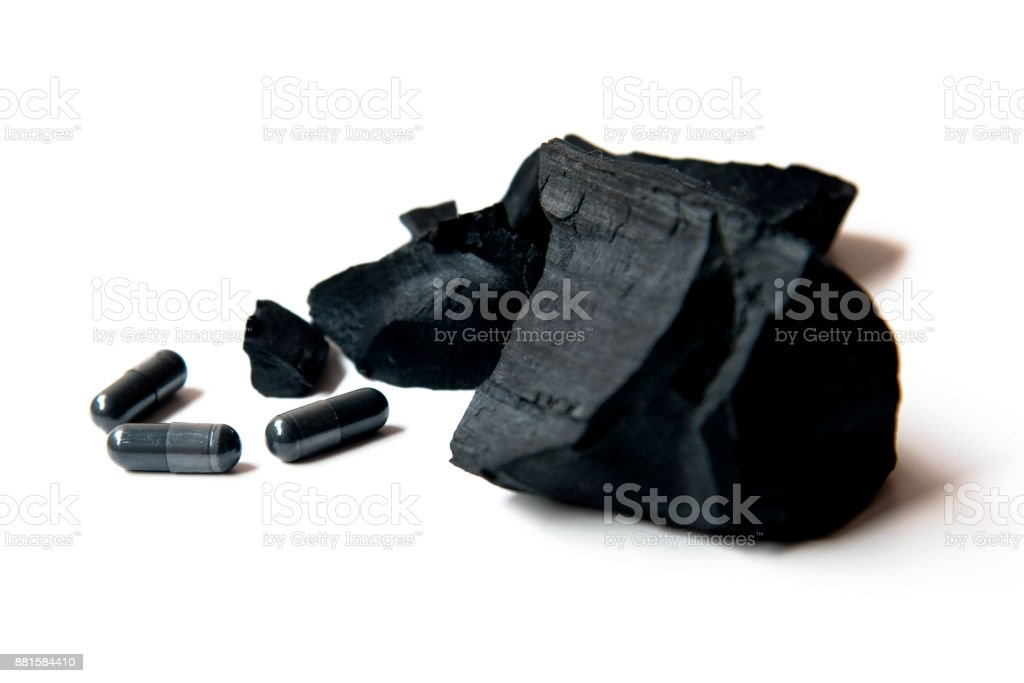 charcoal and activated charcoal capsules isolate on white background stock photo