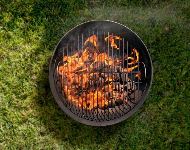 charcoal bbq in the backyard on grass - barbecue grill stock photos and pictures