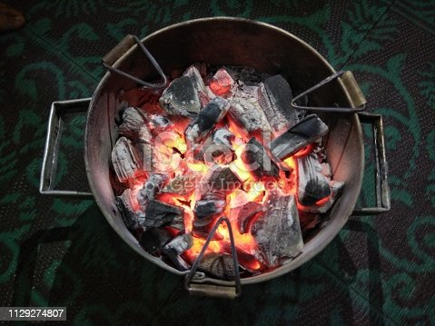 istock Charcoal burning in traditional stove (angeethi in hindi language) in winter season. Cold winter weather 1129274807