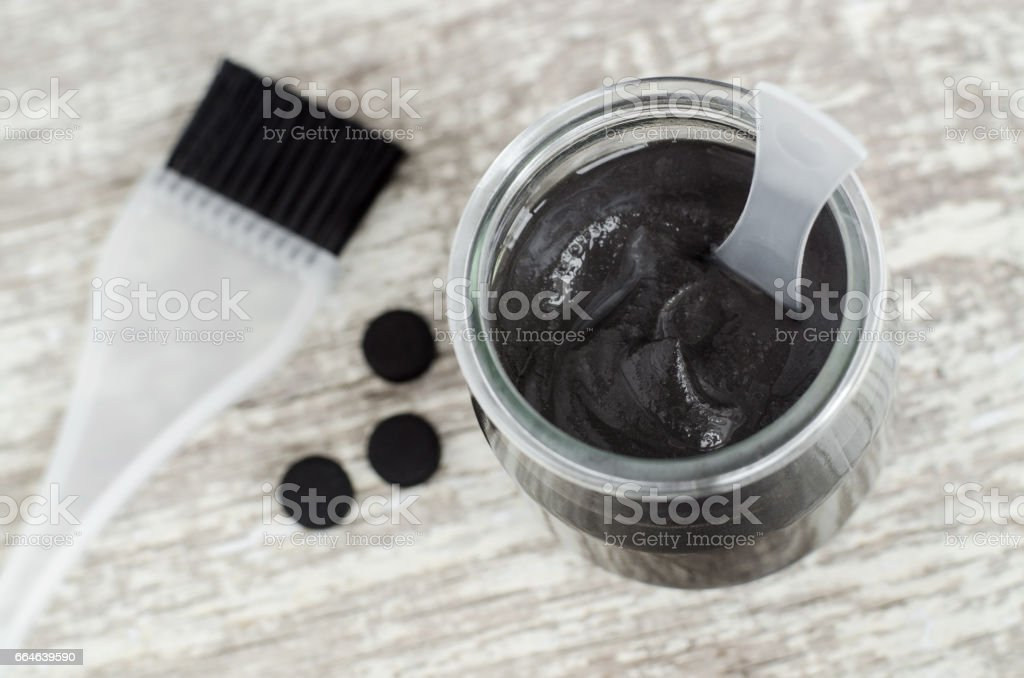 DIY charcoal face and scalp mask (or scrub) in a glass jar. Homemade cosmetics stock photo