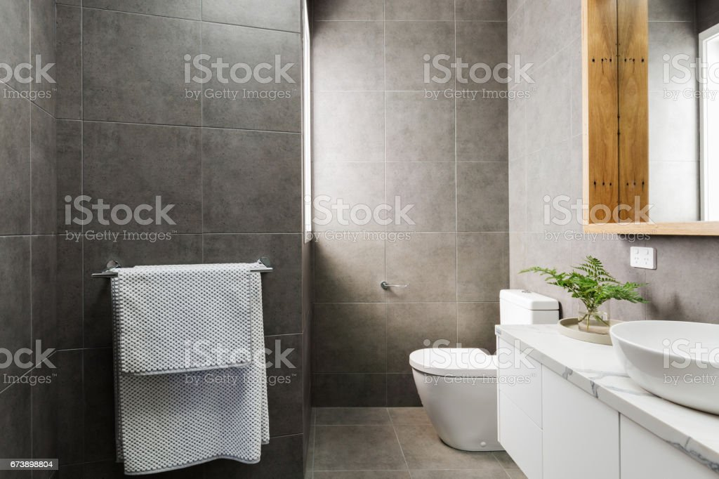 Charcoal grey modern bathroom with marble benchtop and wood mirror stock photo