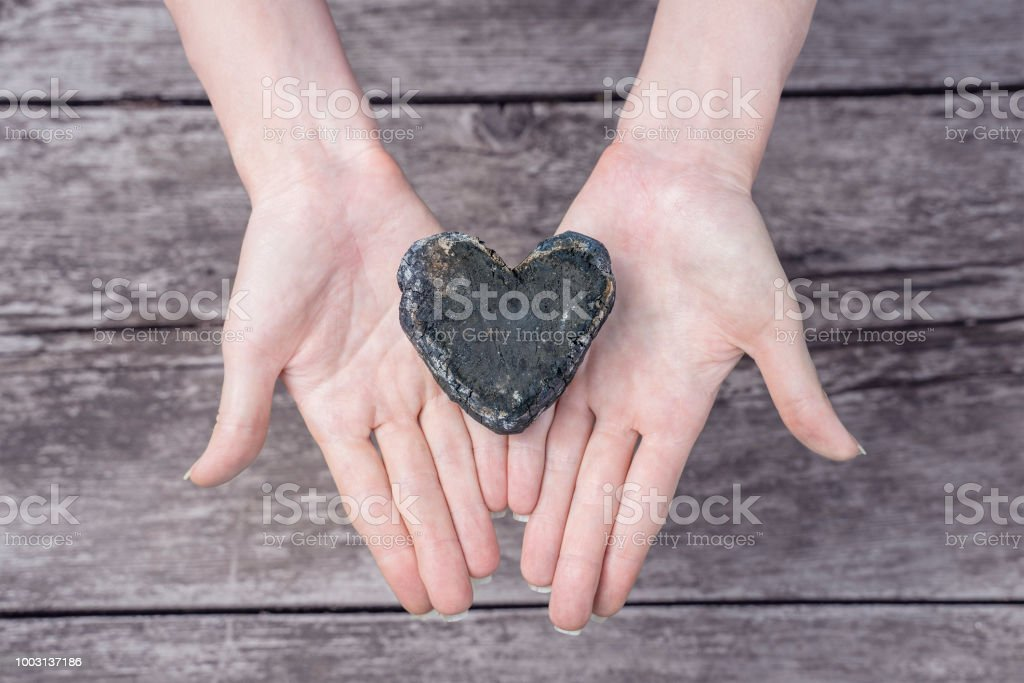 Burning heart of coal in the woman hands given heart concept