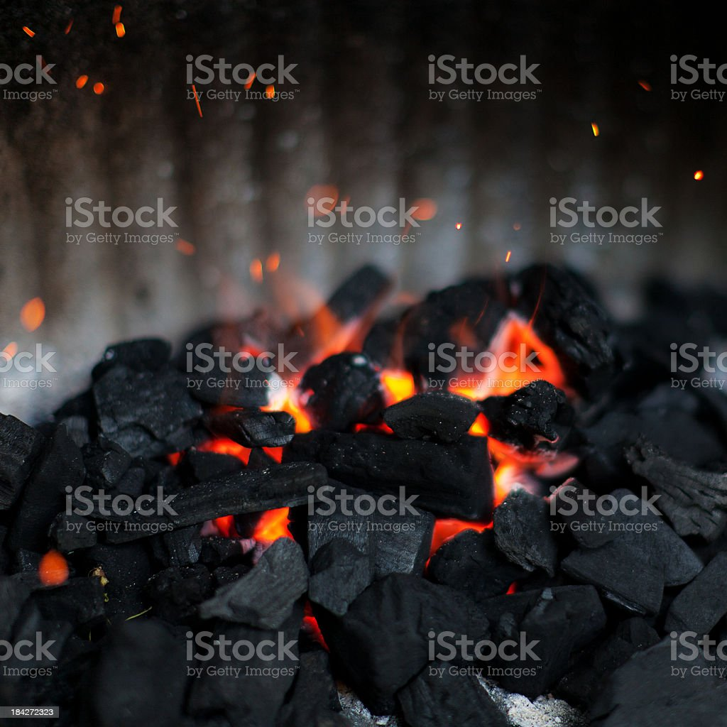 Charcoal pile with fire in the middle stock photo