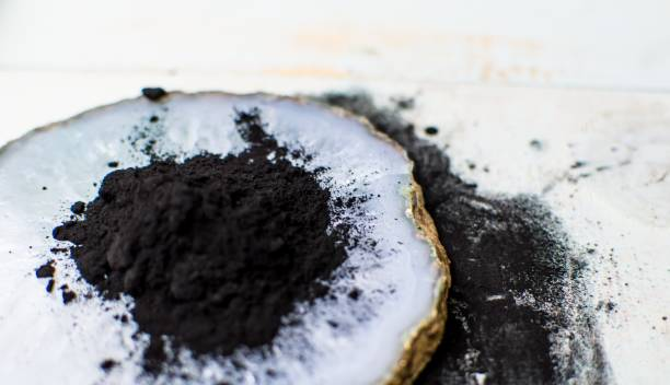 Charcoal Powder on blue Wood background for health and beauty treatment ingredients stock photo