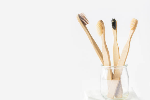 Kohle Holz Bambus Zahnbürsten in Glas tasse auf weißem Hintergrund. Null Abfall Kunststoff frei umweltfreundliche wiederverwendbare Materialien für die Zahnhygiene Gesundheit. Posterbanner – Foto