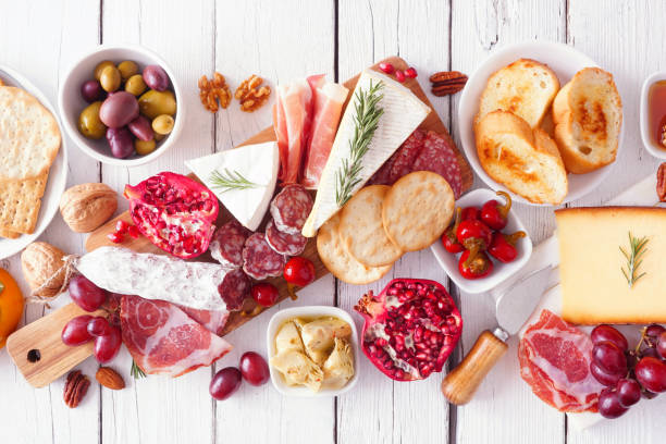 Charcuterie board of assorted cheeses, meats and appetizers, above view table scene over white wood stock photo