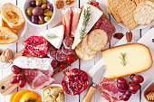 istock Charcuterie board of assorted cheeses, meats and appetizers, top view table scene over white wood 1186420046