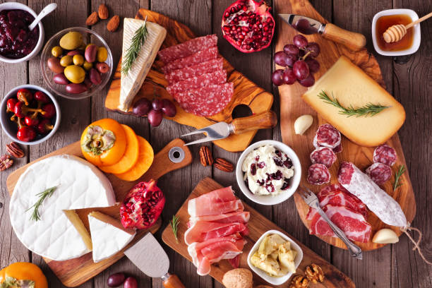 Charcuterie boards of assorted cheeses, meats and appetizers, above view table scene on rustic wood stock photo