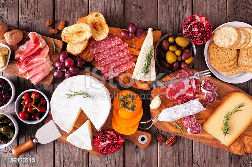 Charcuterie boards of assorted meats, cheeses and appetizers. Top view table scene on a rustic wood background.