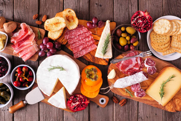 Charcuterie boards of assorted meats, cheeses and appetizers, top view table scene on rustic wood stock photo