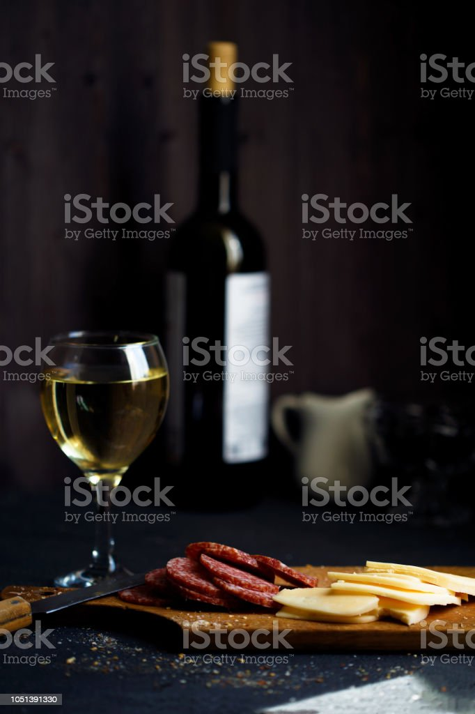 Charcuterie, cheese, salami and a glass of wine on a dark table stock photo