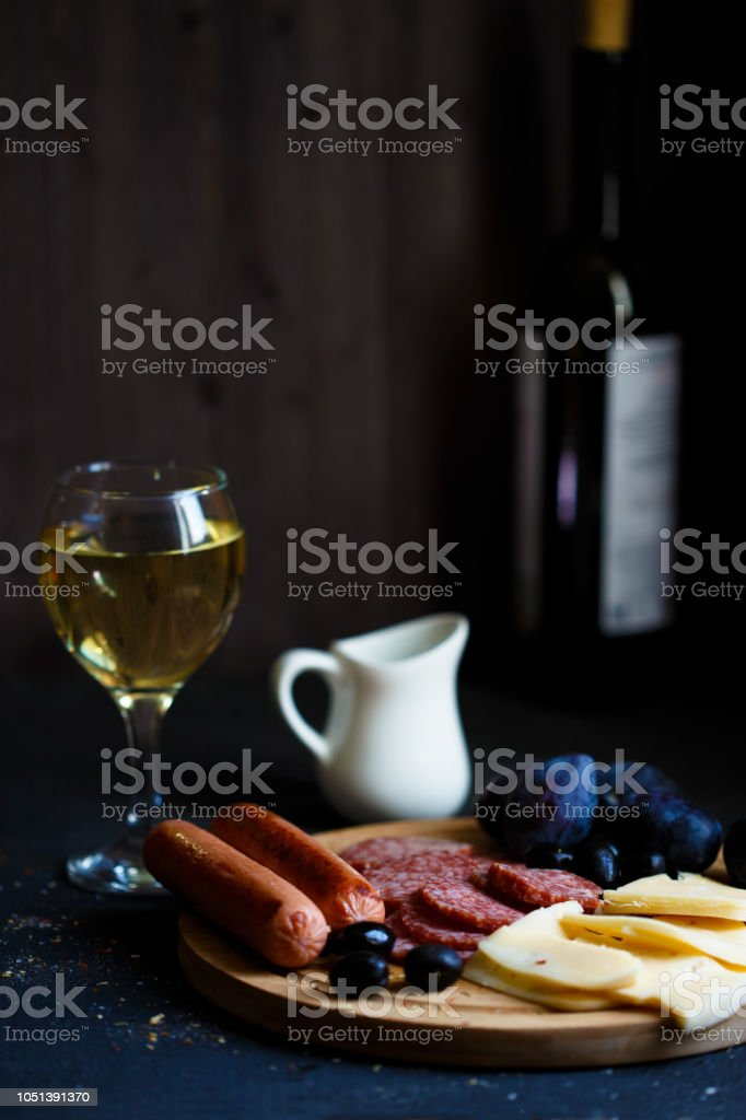Charcuterie, grilled sausages, cheese, salami, plum olives and a glass of wine on a dark table stock photo