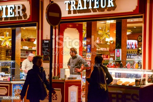 Paris, France - December 26, 2012: Charcutier Traiteur at night, Paris. Cafe and take out restaurant, selling meat products and traditional snacks, like crepes (pancakes). People walking on the street. Waiter is standing outside.