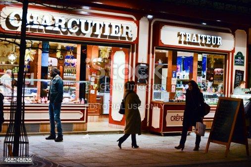Paris, France - December 26, 2012: Charcutier Traiteur at night, Paris. People walking on the street.