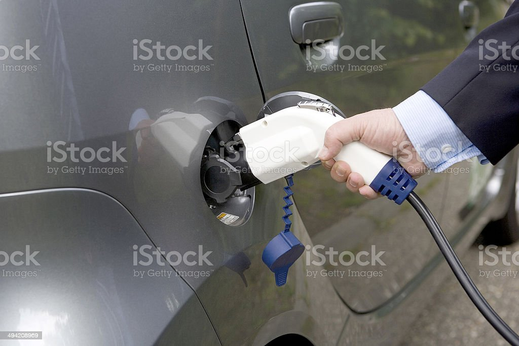 Charge electric car, with hand. stock photo