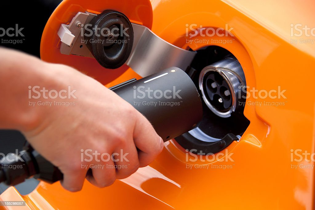 charge orange electric car with hand stock photo