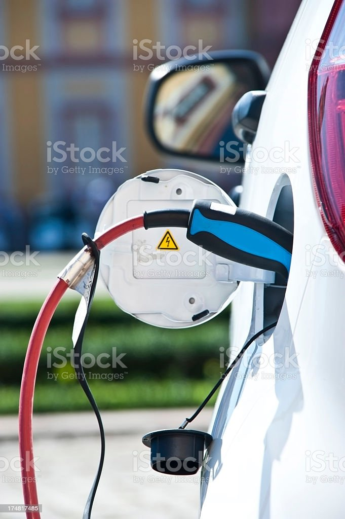 charge white electric car - view from behind stock photo