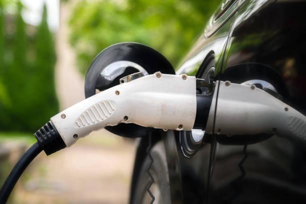 Ladegerät Stecker in Elektroauto in grüner Umgebung Hintergrund. Neues Energiefahrzeug, NEV wird mit Strom beladen. Ökologie, moderne Autos – Foto