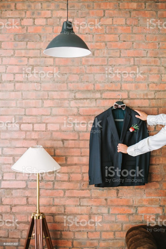 charges on the groom's wedding. the groom's jacket on a brick wall stock photo