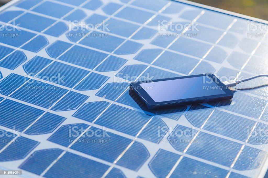 laden ein handy von einem solarpanel stock fotografie und. Black Bedroom Furniture Sets. Home Design Ideas