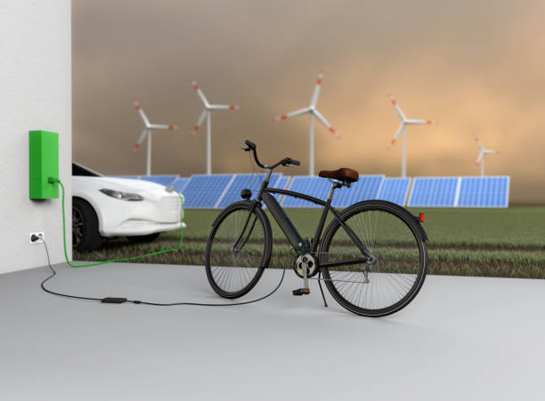 Charging an electric bicycle and an electric car. An electric car and an electric bicycle charge their batteries. Solar panels and wind turbines are in the background. Brandless bicycle and electric car. No real prototypes. charging ebike through solar stock pictures, royalty-free photos & images