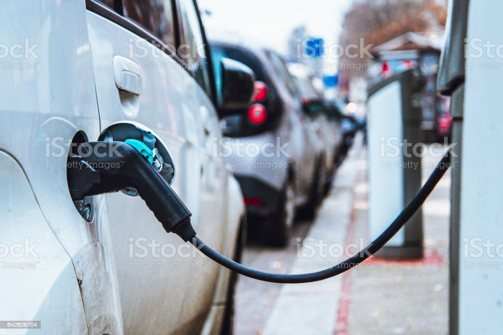 Charging an electric car Electric cars being charged in a street Alternative Fuel Vehicle Stock Photo
