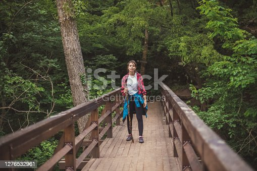 View of a young woman that just came out of the woods, exhausted but super satisfied after a long walk. She's standing on a bridge that represents the border between the wild nature and reality of city life.