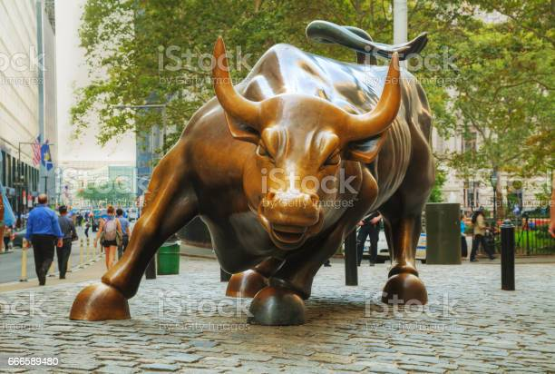 """NEW YORK CITY - September 3: Charging Bull sculpture with people on September 3, 2015 in New York City. The sculpture is both a popular tourist destination, as well as """"one of the most iconic images of New York""""."""