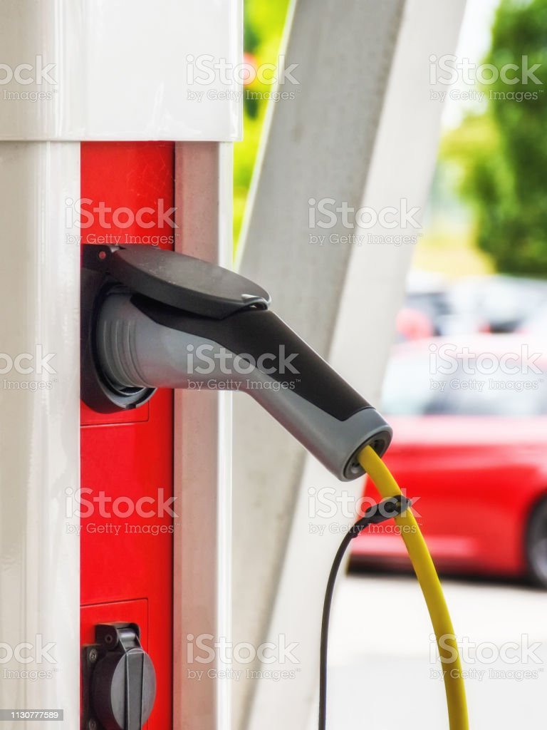 A charging cable for electric vehicles is plugged into a red-white...